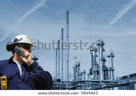 engineer talking in phone with a large blue toned oil and gas refinery in background - stock photo