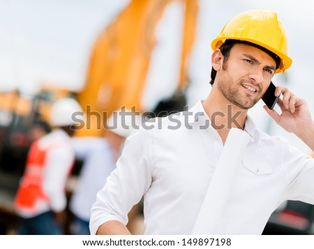 Engineer talking on the phone on a construction site  - stock photo