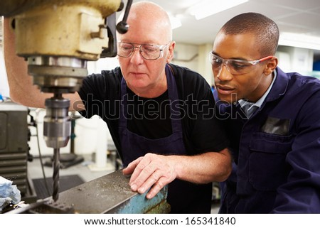 Engineer Teaching Apprentice To Use Milling Machine - stock photo
