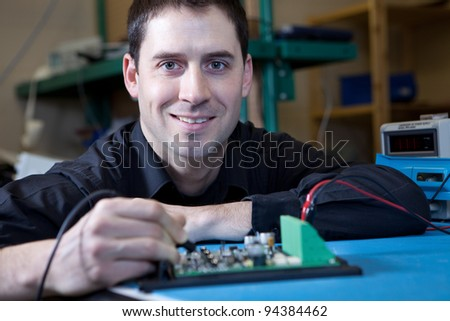 Engineer testing a circuit board assembly - stock photo