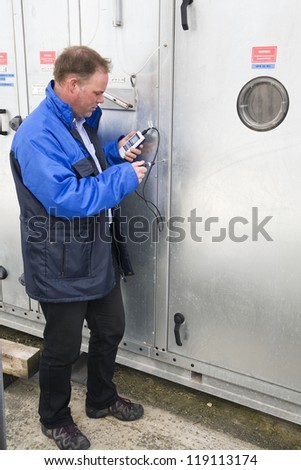 Engineer testing temperature of a ventilation unit. - stock photo