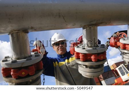 engineer turning pipelines, photographed from underneath - stock photo