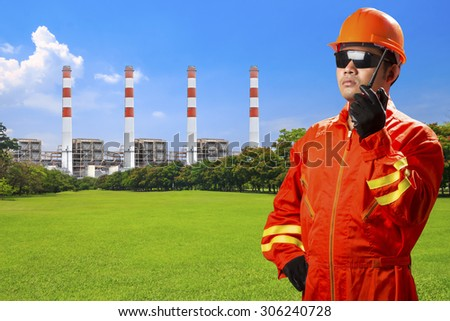 Engineer use radio communication for command working at modern thermal power plants and electric high voltage towers with green park ecology - stock photo