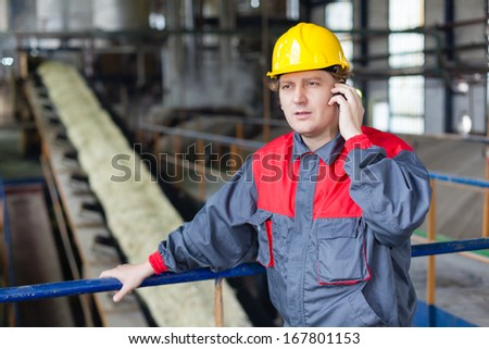 Engineer using a mobile phone in the front of sugar production line