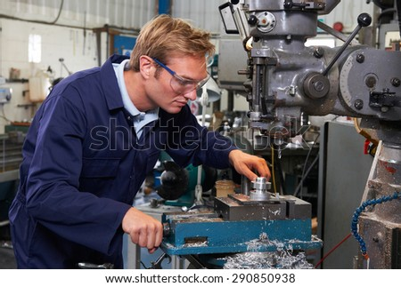 Engineer Using Drill In Factory