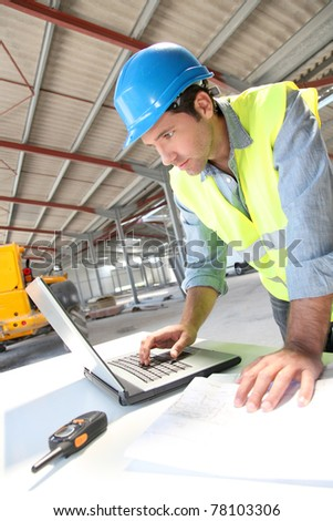 Engineer using laptop computer on construction site - stock photo