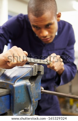 Engineer Using Metal File On Factory Floor