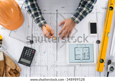 Engineer using set square to draw a line on the blueprint - stock photo