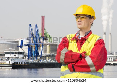 Engineer, wearing safety gear standing with his arms crossed and a confident, proud look on his face in front of an industrial harbor - stock photo