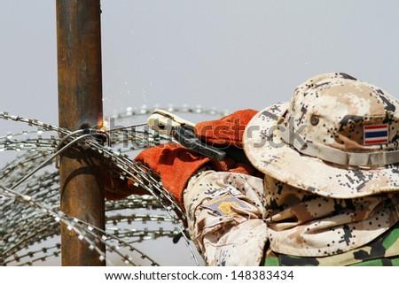 Engineer welding wire fence - stock photo