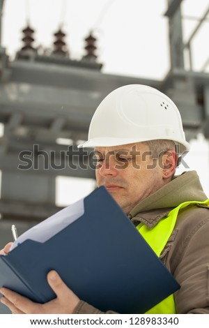 Engineer with folder on a transformer background - stock photo
