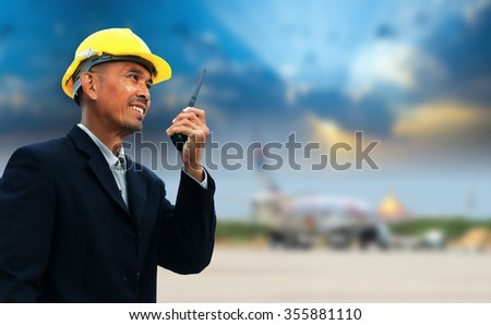 Engineer with his walky-talky stand over airstrip at the airport. - stock photo