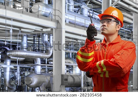Engineer with radio communication in action for working with equipments and machinery in a modern thermal power plant - stock photo