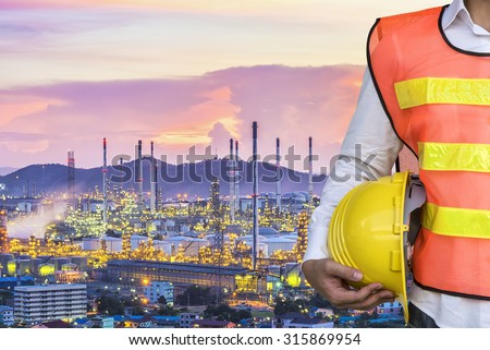 engineer with safety helmet in front of Oil refinery and oil tank - stock photo
