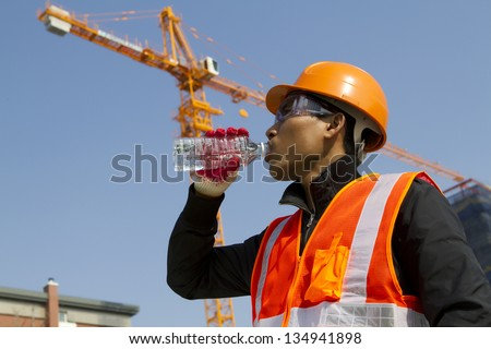 Engineer with safety vest drinking water under construction - stock photo