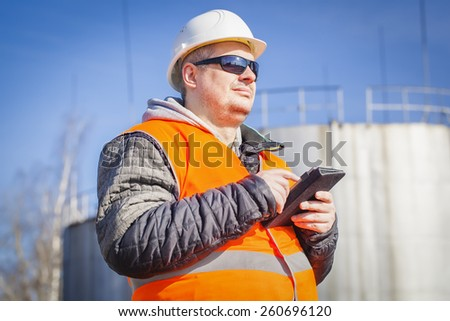 Engineer with tablet PC with oil tank in the background - stock photo