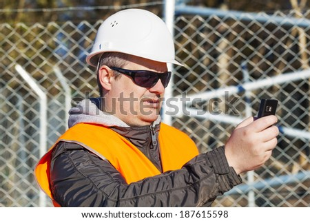 Engineer with the cell phone near to the fence - stock photo