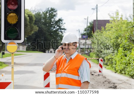 Engineer with the phone near the traffic lights - stock photo