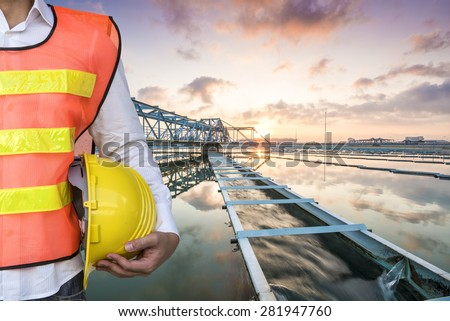 Engineer with The Solid Contact Clarifier Tank type Sludge Recirculation process in Water Treatment Plant with Sun Rise - stock photo