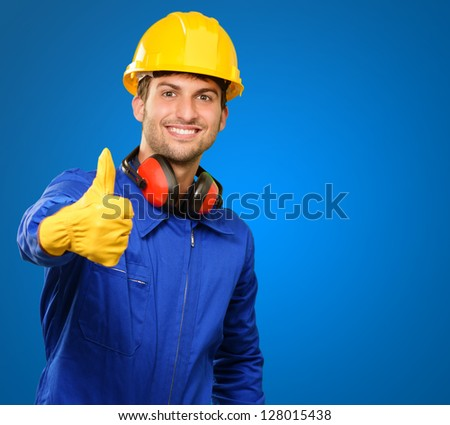 Engineer With Thumb Up Sign Isolated On Blue Background - stock photo