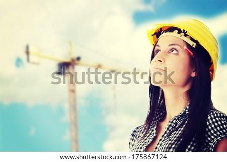 Engineer woman in yellow helmet looking up i - stock photo