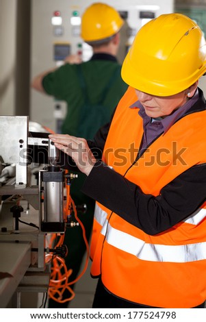 Engineer woman working on professional factory machine