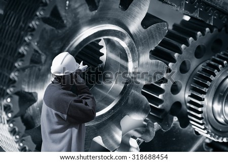 engineer, worker pointing at giant cogwheels and gears machinery, titanium and steel in blue toning . - stock photo