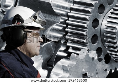engineer, worker with large gears and cogwheels in background - stock photo
