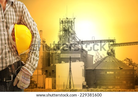engineer working against corn dryer silos and beautiful sunset sky in concept of industrial and engineering - stock photo