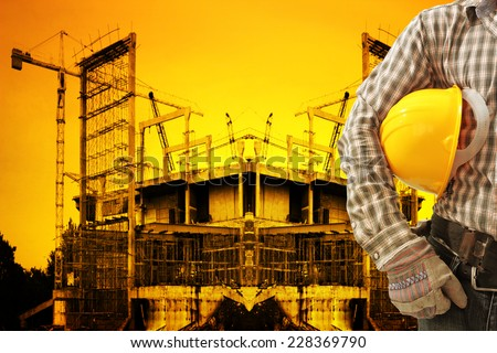 engineer working at building construction site against beautiful sunset - stock photo