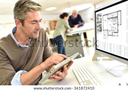 Engineer working in design office on desktop computer - stock photo