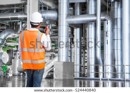 engineer working in thermal power plant with talking on the walkie talkie for controlling work - Power Plant Engineer