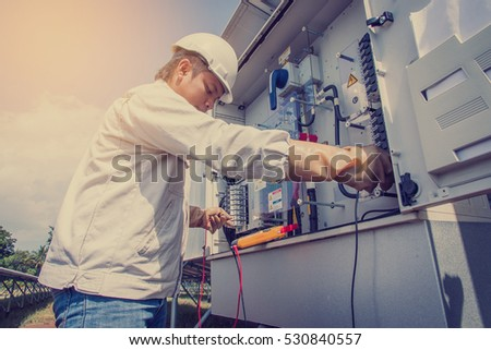 engineer working on checking and maintenance equipment at green energy solar power plant: checking status inverter