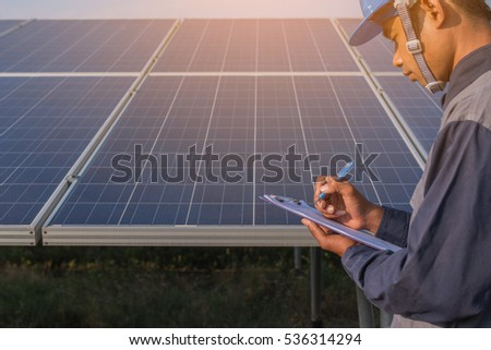 engineer working on checking and maintenance equipment at green energy solar power plant: checking structure and solar panel