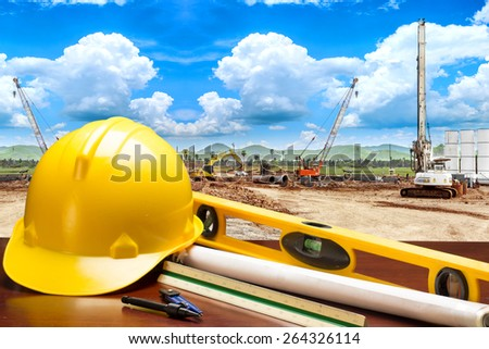 engineer working table plan and blueprints in building construction site against blue sky  - stock photo