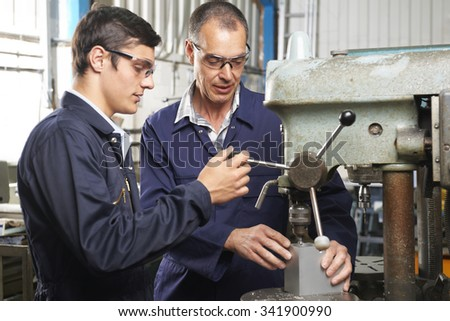 Engineer Working With Apprentice Using Drill