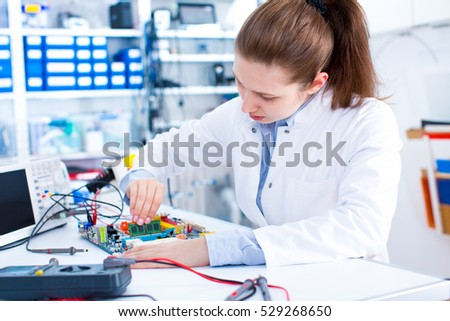 Engineer working with circuits. A woman engineer solders circuits sitting at a table.  Microchip production factory. Technological process. Assembling the PCB board.