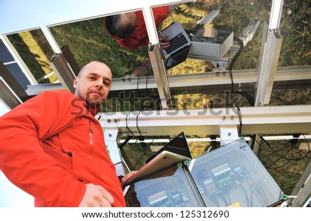 Engineer working with laptop fixing  solar panels - stock photo