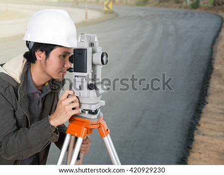 engineer working with survey equipment theodolite with road under construction background - stock photo