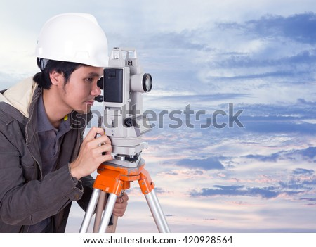 engineer working with survey equipment theodolite with sky at sunset