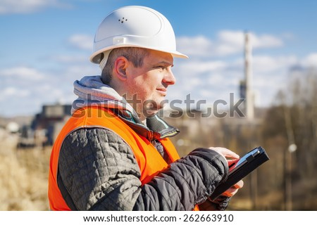 Engineer working with tablet PC near factory