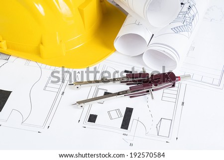 Engineer workplace with blueprints, compass  and safety helmet - stock photo