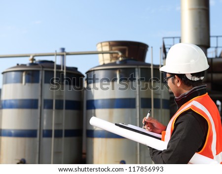 engineer  write on notepad with large industry background
