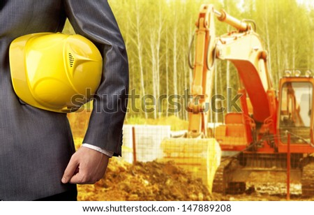 engineer yellow helmet for workers security against the background of the excavator bucket rake in a layer of earth - stock photo