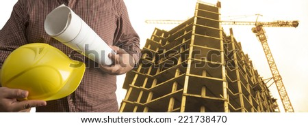 engineer yellow helmet for workers security on background of new high-rise apartment buildings and construction cranes and evening sunset sky Copy space for inscription No face Unrecognizable person - stock photo