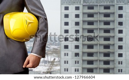 engineer yellow helmet for workers security on the background of a new high-rise apartment buildings of gray - stock photo