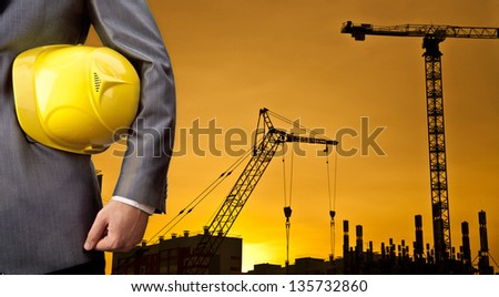 engineer yellow helmet for workers security on the background of a new high-rise apartment buildings and construction cranes and evening sunset sky - stock photo
