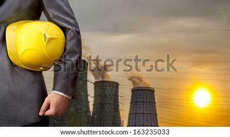 engineer yellow helmet for workers security over Central Electric Heat CHP in winter