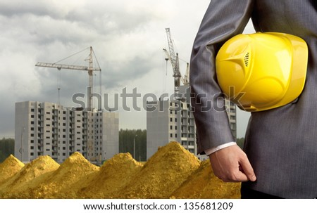 engineer yellow helmet for workers security over new houses and crane background