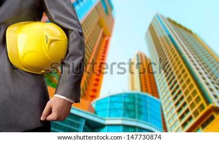 engineer yellow helmet for workers security over two high-rise buildings - stock photo